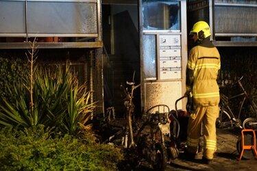 Scooters in brand bij portiek flat in Den Helder