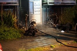 Scooters in brand bij portiek flat in Den Helder